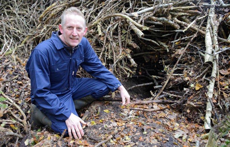 Veehouder Tom van der Bosch uit Lippenhuizen heeft veel last van dassen. Op de foto zit hij bij een ingang van een van de dassenburchten op zijn land. Foto: Marten Sandburg