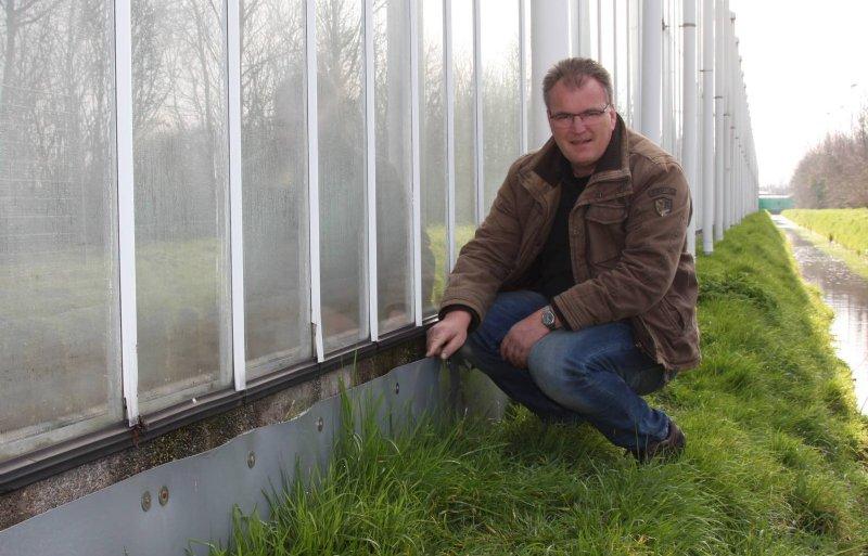 Tomatenteler Teun Varekamp uit De Lier toont het pvc-doek tegen de kasvoet, dat overstromend water moet tegenhouden.