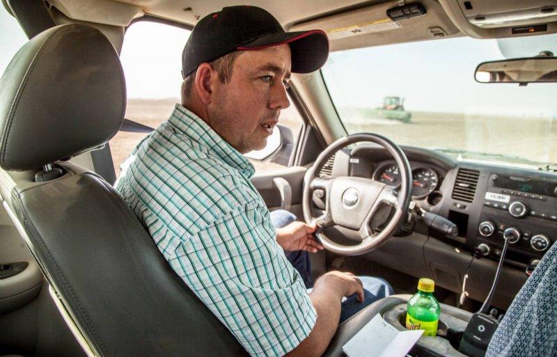Wiebren Jonkman rijdt langs een perceel waar een van zijn mensen aan het werk is.