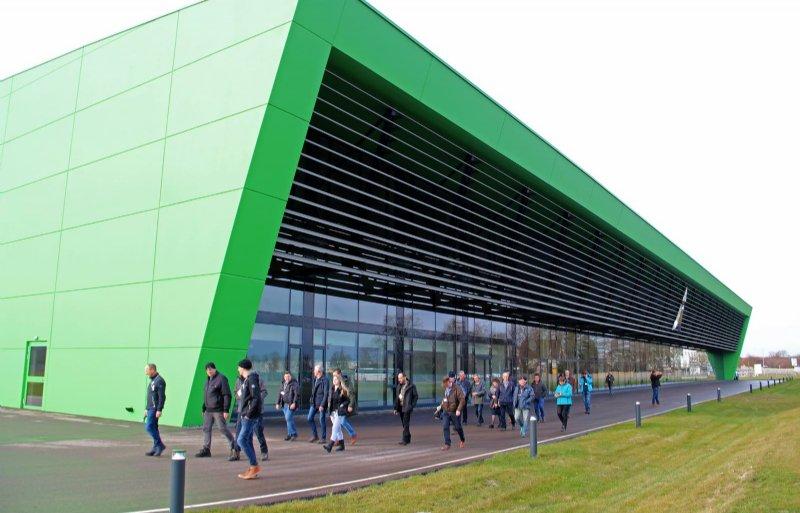 Lezers van Nieuwe Oogst lopen voor de voorgevel van de fabriek, die de vorm en kleur heeft van een Deutz-Fahr motorkap.