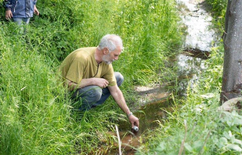 Henk Dekker neemt een watermonster uit de sloot.