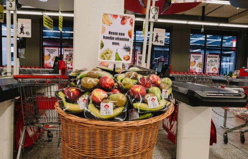 Wekelijks wisselende fruitpakketten in met groente en fruit bedrukte manden moeten stimuleren tot impulsaankoop.