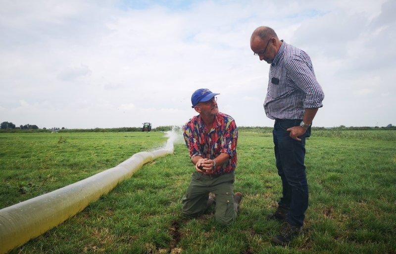Niek Bosma (links) van Wetterskip Fryslân en loonwerker Arjen Rijpma bekijken de muizenschade bij Hommerts.