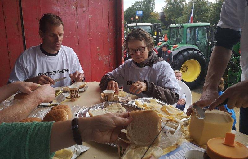 Boeren smeren broodjes op de kar.