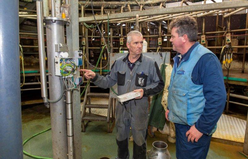 Pieter Schouten overlegt met monteur Jaap Bloemendaal over het onderhoud aan zijn carrouselmelkstal.