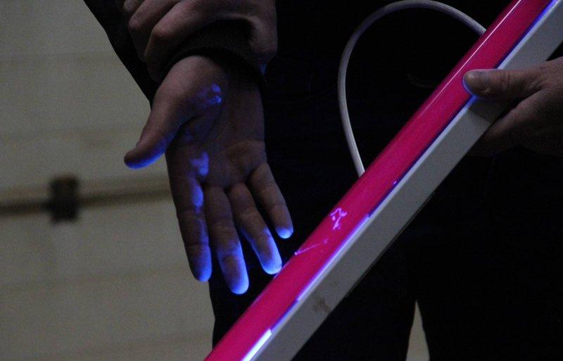 Fluoriserende vloeistof en uv-licht maken duidelijk dat je handschoenen moet dragen bij het schoonmaken van een spuitdop.