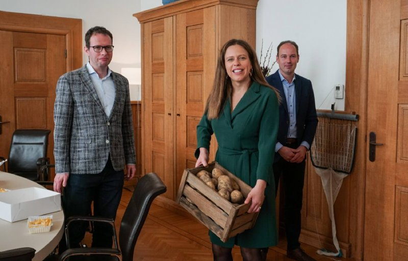 André Hogendijk (links) en Hendrik Jan ten Cate overhandigen minister Carola Schouten een kist aardappelen van het land van Ten Cate.