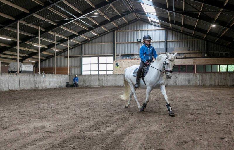 Rinkse van der Bijl rijdt met pony Puk in de nieuwe manege van haar ouders op Schiermonnikoog. De manege was net klaar, toen het RIVM met coronamaatregelen kwam.