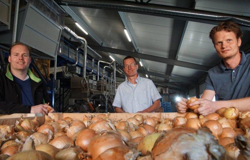 Joost Jonk van VanAndelBio, Harrie Versluis van DLV Advies en Bas Groeneveld, die uien teelt met Sjaak Twisk in Dronten. Foto's: Jorg Tönjes
