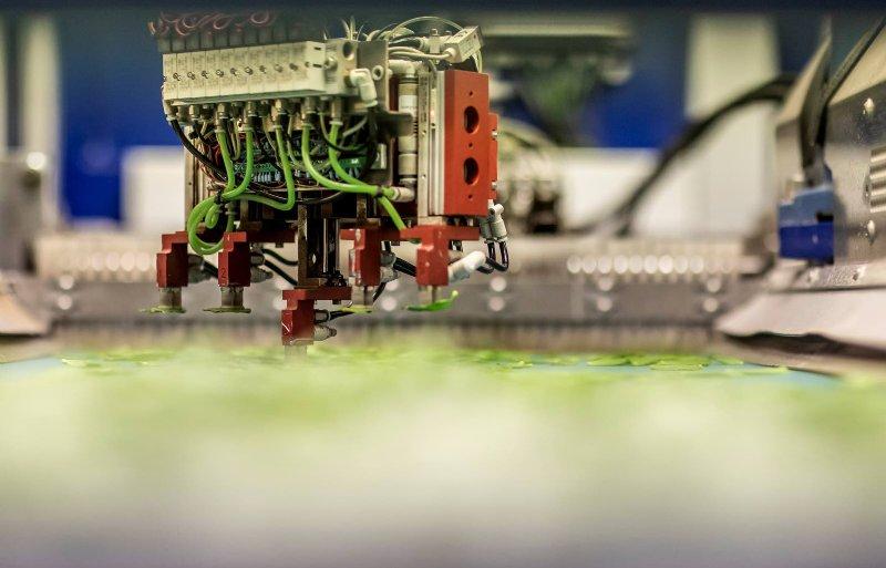 De steksteekrobot pakt stekjes op van de lopende band.