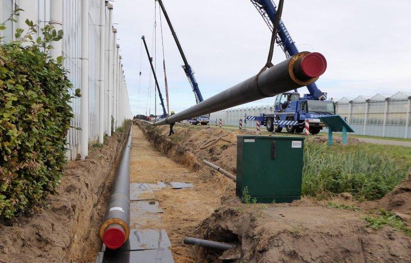 Hijsen van buizen bij de aanleg van het warmtenet naar glastuinbouwbedrijven in Koekoekspolder.