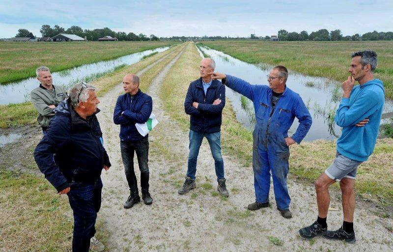 Boeren praten met hoogheemraad Schenk (links).