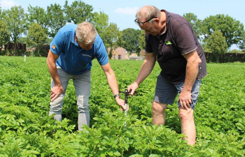 Geert-Jan van Roessel (links) en Jos van Sambeeck controleren de stabiliteit van een standpijp met sprinkler.