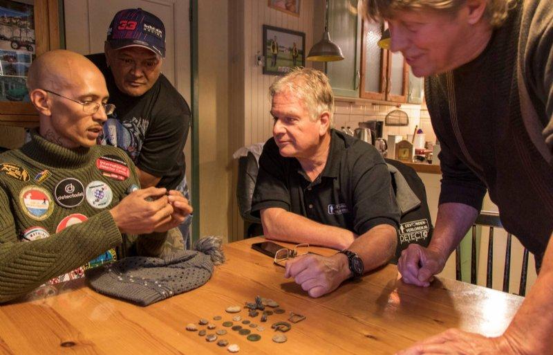 Justin Nuruwe toont zijn waardevolle vondsten aan zijn vader, collega-detectorist Richard Ober en boer Herman Jansen (uiterst rechts).